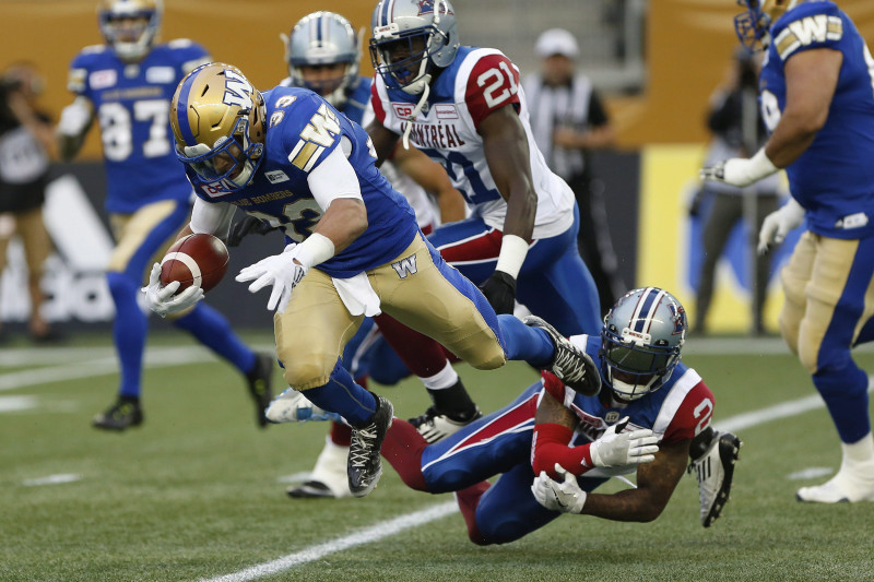 Despite Montreal Alouettes' Jovon Johnson (2) getting a hand on Winnipeg Blue Bombers' Andrew Harris (33) he can't stop the running back during the first half of pre-season CFL action in Winnipeg Wednesday, June 8, 2016. THE CANADIAN PRESS/John Woods