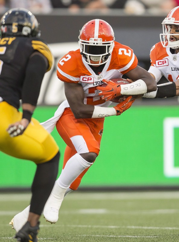 BC Lions' Chris Rainey, centre, takes the handoff from quarterback Jonathon Jennings during first half CFL action against the Hamilton Tiger Cats at Tim Hortons Field in Hamilton on Friday, July 1, 2016. THE CANADIAN PRESS/ Geoff Robins