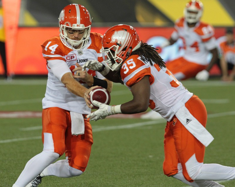 Lions' quarterback Travis Lulay hands off to Shaquille Murray-Lawrence during fourth quarter CFL action in Hamilton on Friday, July 1st, 2016. (CFL PHOTO - Dave Chidley)
