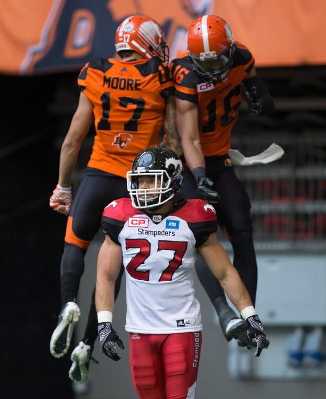 Calgary Stampeders' Jeff Hecht, front, walks to the bench as B.C. Lions' Nick Moore, back left, and Bryan Burnham celebrate Burnham's touchdown during the first half of a pre-season CFL football game in Vancouver, B.C., on Friday June 17, 2016. THE CANADIAN PRESS/Darryl Dyck