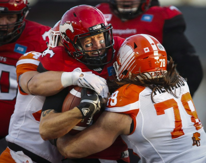 BC Lions' Adam Bighill, left, and David Menard, right sack Calgary Stampeders' quarterback Bo Levi Mitchell during first half CFL football action in Calgary, Friday, July 29, 2016.THE CANADIAN PRESS/Jeff McIntosh