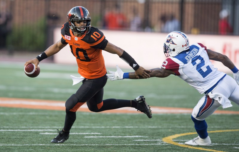 B.C. Lions quarterback Jonathon Jennings looks for a receiver as he is rushed by Montreal Alouettes cornerback Jovon Johnson during first quarter CFL football action Thursday, August 4, 2016 in Montreal. THE CANADIAN PRESS/Paul Chiasson
