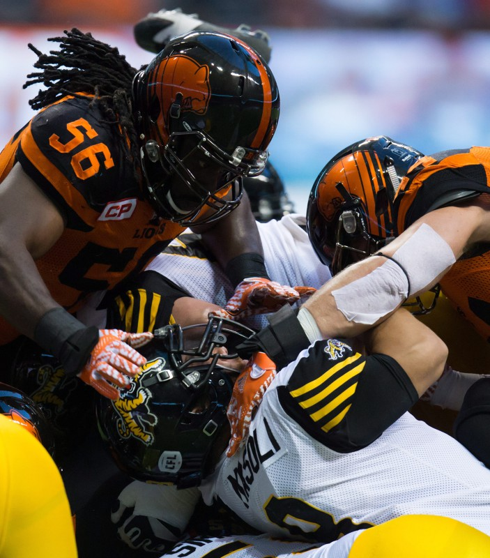 B.C. Lions' Solomon Elimimian, left, and Adam Bighill, right, tackle Hamilton Tiger-Cats' quarterback Jeremiah Masoli (8) during the first half of a CFL football game in Vancouver, B.C., on Saturday August 13, 2016. THE CANADIAN PRESS/Darryl Dyck