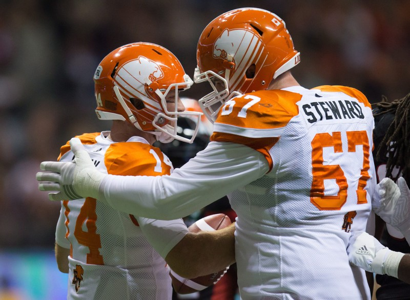 B.C. Lions' quarterback Travis Lulay, left, and Hunter Steward celebrate Lulay's touchdown against the Ottawa Redblacks during the first half of a CFL football game in Vancouver, B.C., on Saturday October 1, 2016. THE CANADIAN PRESS/Darryl Dyck