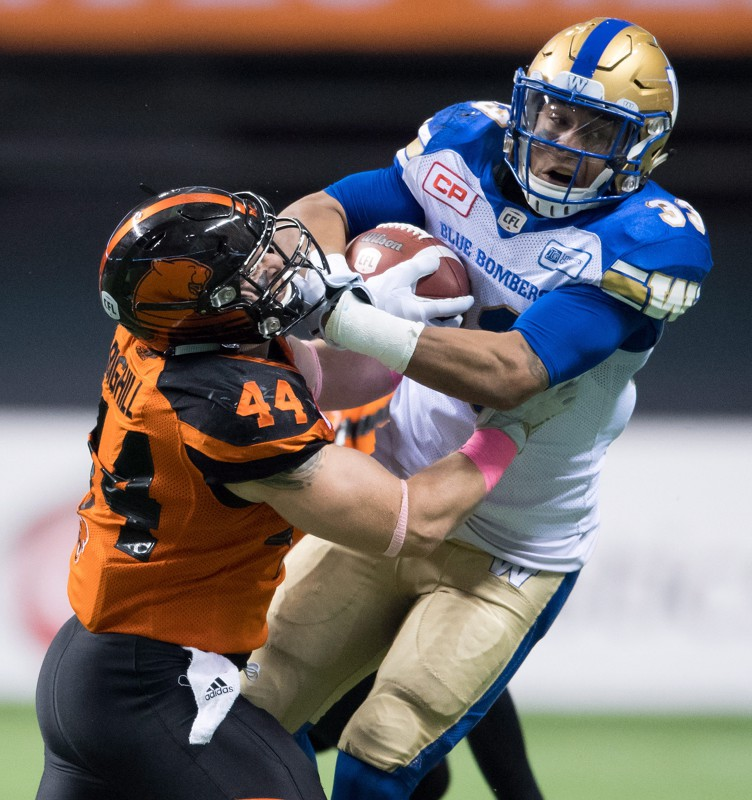B.C. Lions' Adam Bighill, left, tackles Winnipeg Blue Bombers' Andrew Harris as he carries the ball during the first half of a CFL football game in Vancouver, B.C., on Friday October 14, 2016. THE CANADIAN PRESS/Darryl Dyck