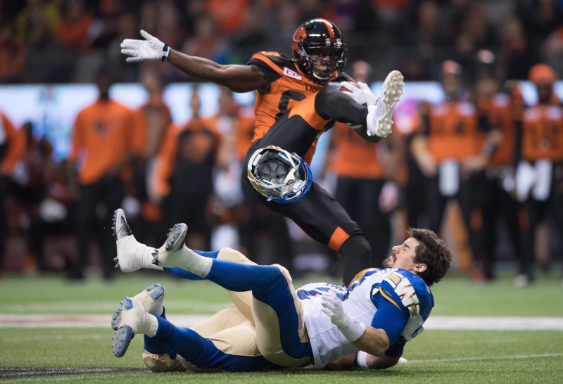 Winnipeg Blue Bombers' Ian Wild, bottom, loses his helmet after colliding with B.C. Lions' Stephen Adekolu, top, and teammate Khalil Bass, back, during first half western semifinal CFL football action in Vancouver, B.C., on Sunday November 13, 2016. THE CANADIAN PRESS/Darryl Dyck