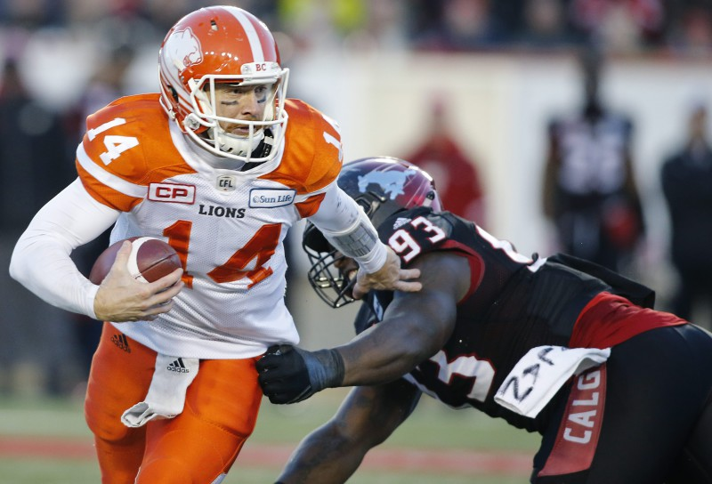 B.C. Lions' quarterback Travis Lulay, left, breaks a tackle attempt by Calgary Stampeders' Micah Johnson during second half CFL Western Final football action in Calgary, Alberta on Sunday, Nov. 20, 2016. (CFL PHOTO - Larry MacDougal)