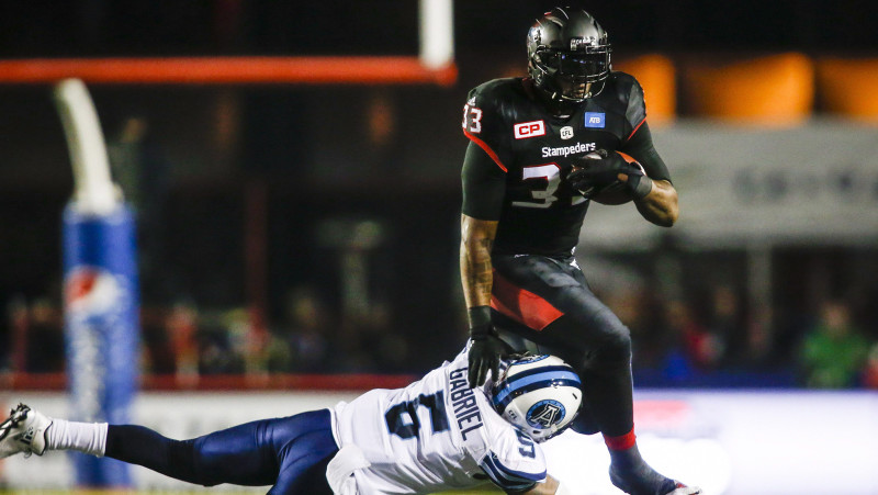 Toronto Argonauts' Brian Jones, left, tackles Calgary Stampeders' Jerome Messam during first half CFL football action in Calgary, Friday, Oct. 21, 2016.THE CANADIAN PRESS/Jeff McIntosh
