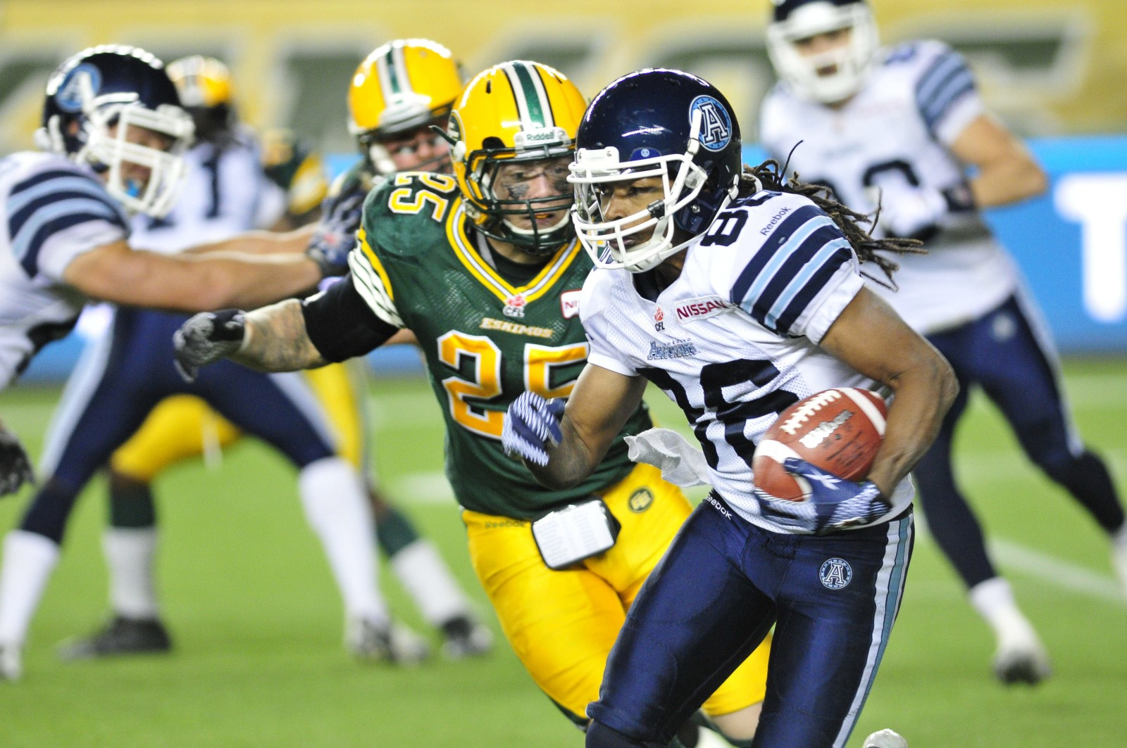 left to right - Edmonton Eskimos player #25 (S ) Mike Miller tries to go after Toronto Argonauts player # 86 ( WR)Trent Guy during the 4th quarter of CFL game action between the Edmonton Eskimo's and the Toronto Argonauts at Commonwealth stadium in Edmonton Saturday, September 28/2013 (CFL PHOTO - Walter Tychnowicz)