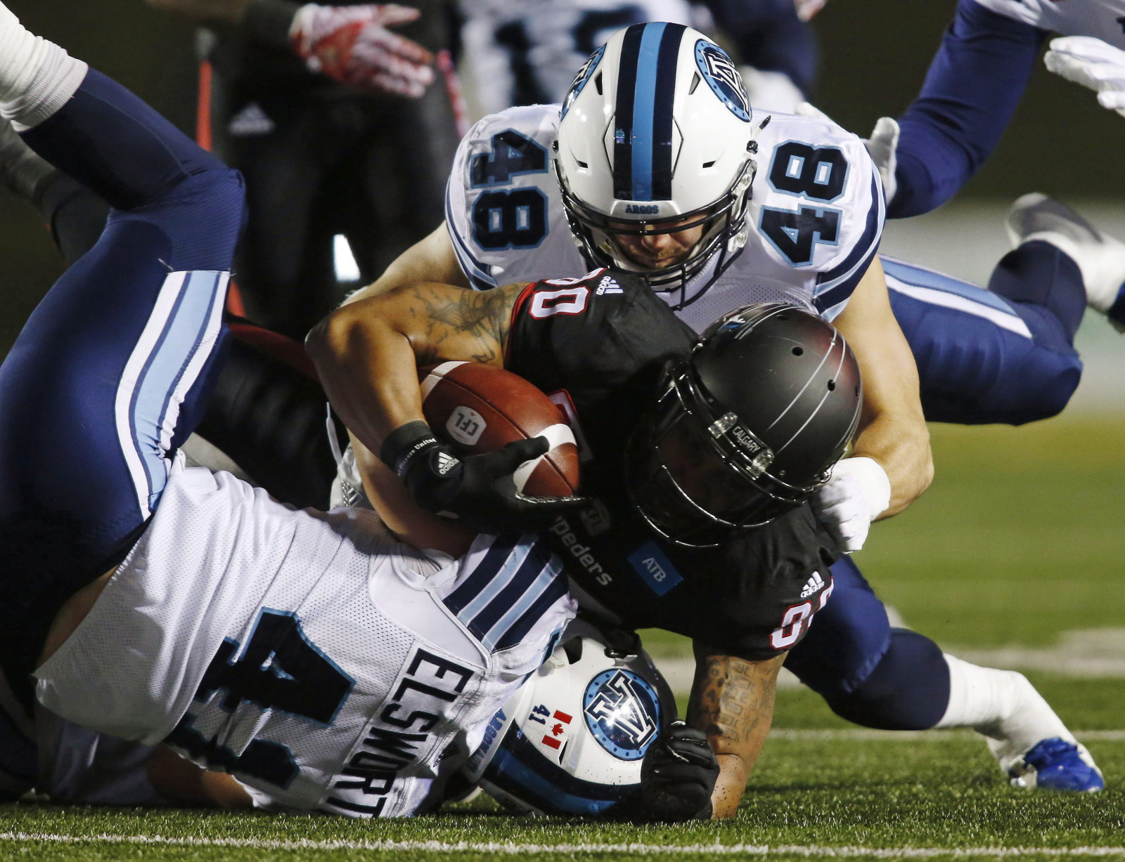 Toronto Argonauts' Thomas Miles, top, tackles Calgary Stampeders' Jamal Nixon during first half CFL football action in Calgary, Friday, Oct. 21, 2016.THE CANADIAN PRESS/Jeff McIntosh