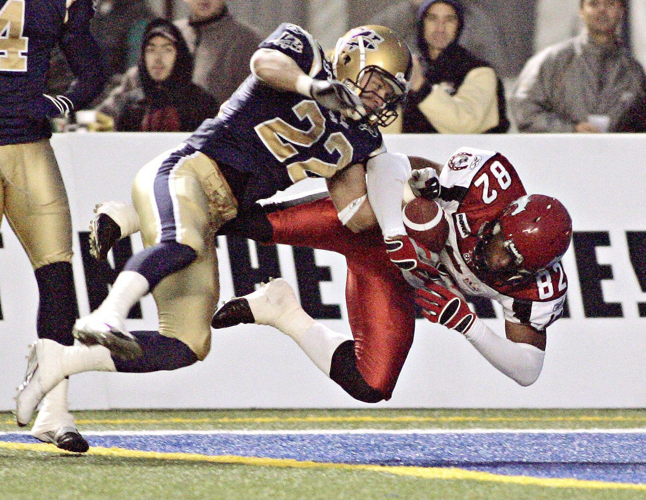 Calgary Stampeders' Nikolas Lewis (82) gets a touchdown as he collides with Winnipeg Blue Bombers' Shawn Gallant (22) during the second half CFL action in Winnipeg, on Sunday, August 30, 2005. (CP PHOTO/Marianne Helm)