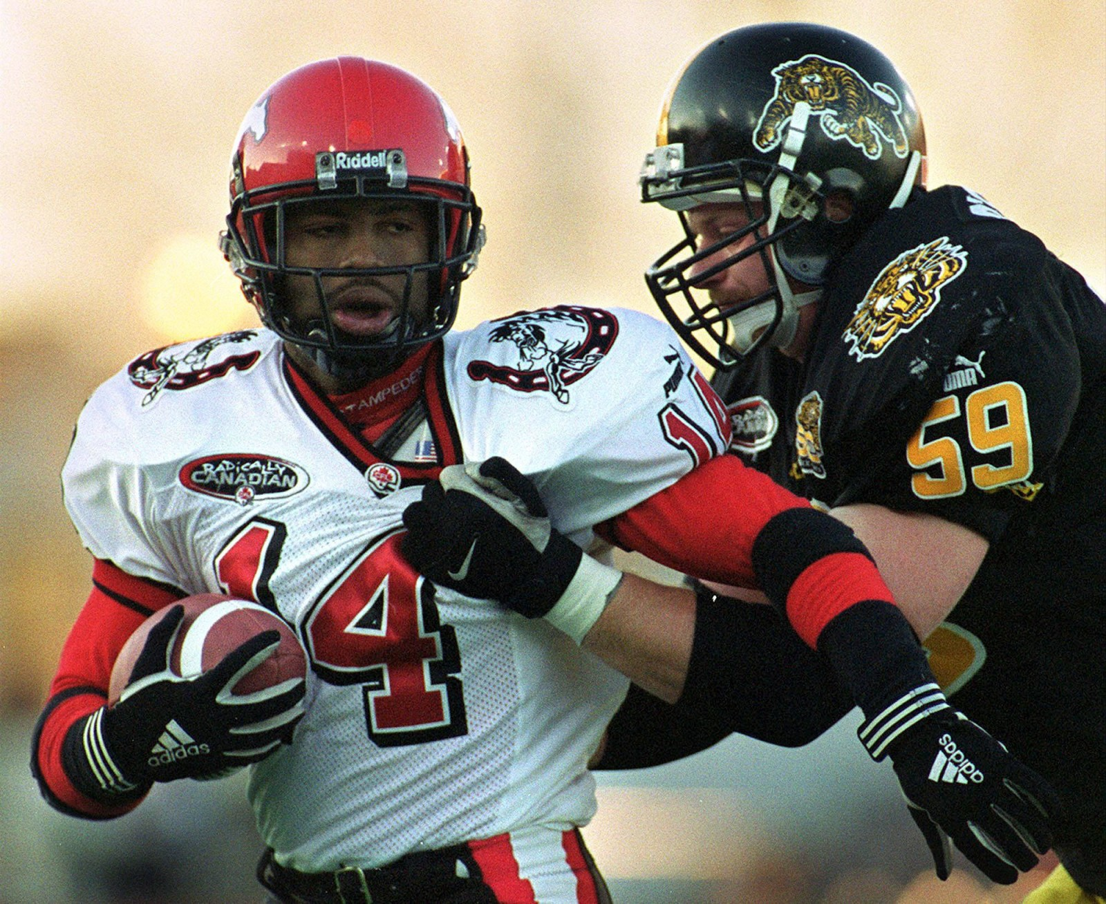 Hamilton Tiger-Cats linebacker Mike O'Shea (59) wraps up Calgary Stampeders runningback Rock Preston (14) during first half CFL action in Hamilton on Sunday Nov. 5, 2000. (CP PHOTO/Frank Gunn)