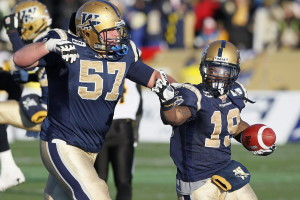Winnipeg Blue Bombers' Chris Garrett (19) and Brendon LaBatte (57) celebrate after Garrett scored a touchdown against the Hamilton Tiger-Cats at the end of the second half of their CFL Eastern Final game in Winnipeg Sunday, November 20, 2011. LaBatte agreed to terms Wednesday with the hometown Roughriders. Contract details weren't immediately divulged but LaBatte's deal will reportedly pay him in the neighbourhood of $200,000 annually. THE CANADIAN PRESS/John Woods