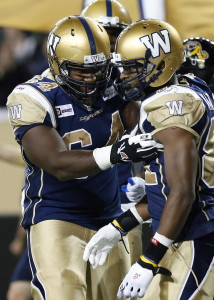 Winnipeg Blue Bombers' Chris Greaves (64) congratulates Cory Watson (81) for his touchdown against the Hamilton Tiger-Cats during the second half of CFL action in Winnipeg Saturday, September 27, 2014. THE CANADIAN PRESS/John Woods