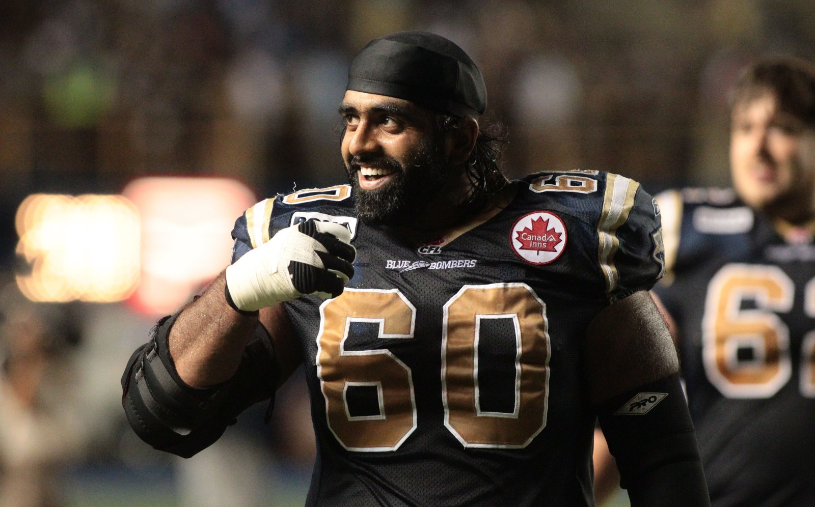 Winnipeg Blue Bombers' Ibrahim Khan (60) smiles to the crowd as he leaves the field after the Winnipeg Blue Bombers 25-20 win over the BC Lions afer fourth quarter CFL action on in Winnipeg on Thursday,  July 28, 2011.  (CFL PHOTO - MARIANNE HELM)