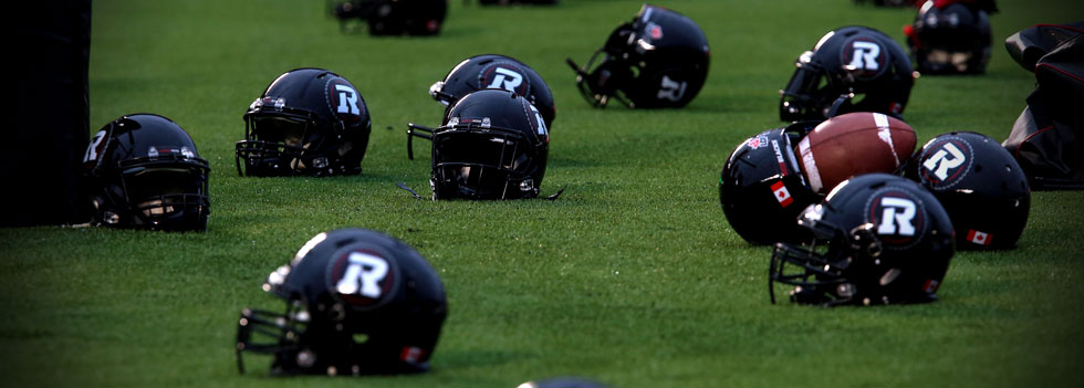 Image of REDBLACKS helmets on the field turf