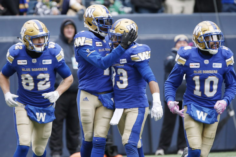 Winnipeg Blue Bombers' Darvin Adams (1) and Andrew Harris (33) celebrate Adams' touchdown against the Saskatchewan Roughriders during the first half of CFL action in Winnipeg Saturday, October 13, 2018. THE CANADIAN PRESS/John Woods