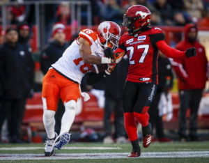 BC Lions' Bryan Burnham, left, manages catch and hang onto the ball as Calgary Stampeders' Tunde Adeleke tries to knock it free during CFL football action in Calgary, Saturday, Oct. 13, 2018. THE CANADIAN PRESS/Jeff McIntosh