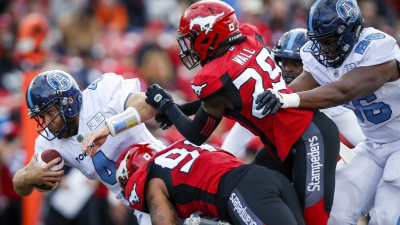 Calgary's defence hauls down Toronto's McLeod Bethel-Thompson in Thursday night's 26-16 win. (The Canadian Press)