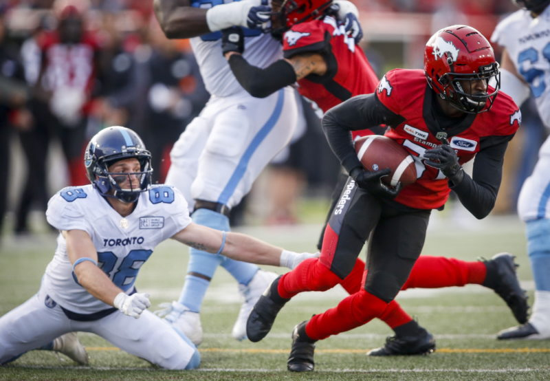 Toronto Argonauts' Jimmy Ralph, left, looks on as Calgary Stampeders' Tre Roberson, picks up a fumbled ball and runs it in for a touchdown during second half CFL football action in Calgary, Thursday, July 18, 2019. THE CANADIAN PRESS/Jeff McIntosh