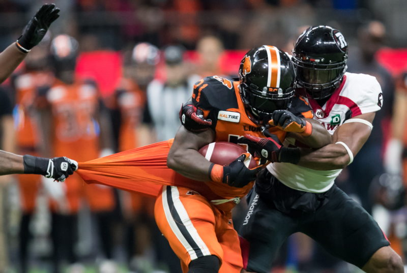 B.C. Lions' Brandon Rutley, front, carries the ball in front of Ottawa Redblacks' Jeff Knox Jr., back right, as Avery Ellis, not seen, pulls on his jersey during the first half of a CFL football game in Vancouver, on Friday September 13, 2019. THE CANADIAN PRESS/Darryl Dyck