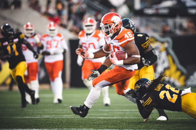 Rolly Lumbala (46) of the BC Lions and Ethan Davis (26) of the Hamilton Tiger-Cats during the game at Tim Hortons Field in Hamilton, ON., on Saturday, July 15, 2017. (Photo: Johany Jutras)