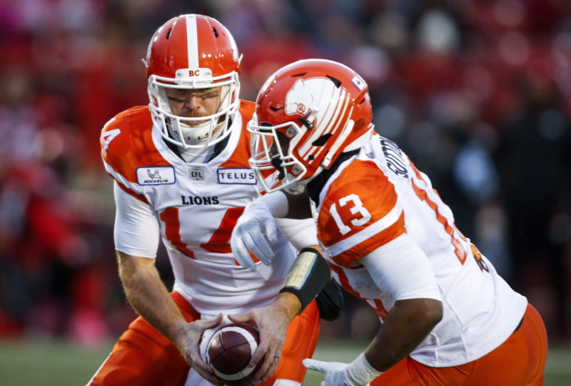 BC Lions quarterback Travis Lulay, left, hands the ball off to Tyrell Sutton, during CFL football action against the Calgary Stampeders, in Calgary, Saturday, Oct. 13, 2018. THE CANADIAN PRESS/Jeff McIntosh