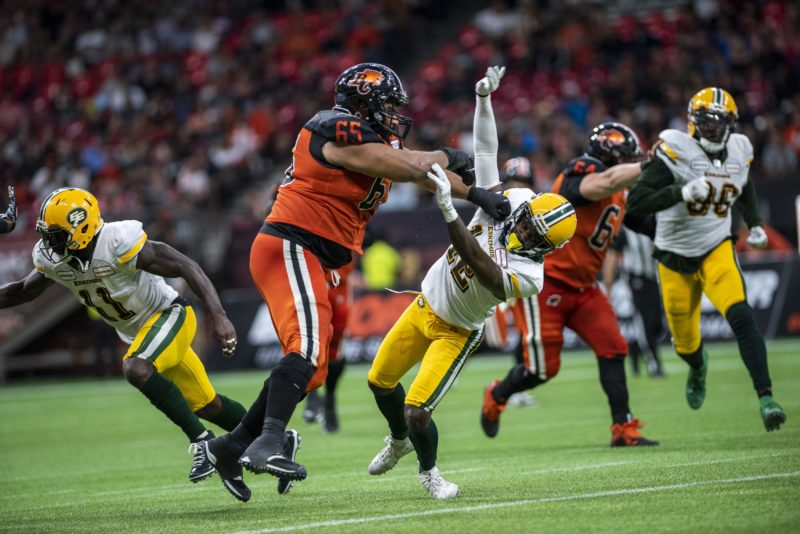 BC Lions' star lineman Sukh Chungh tosses a defender during a game with the Edmonton Eskimos