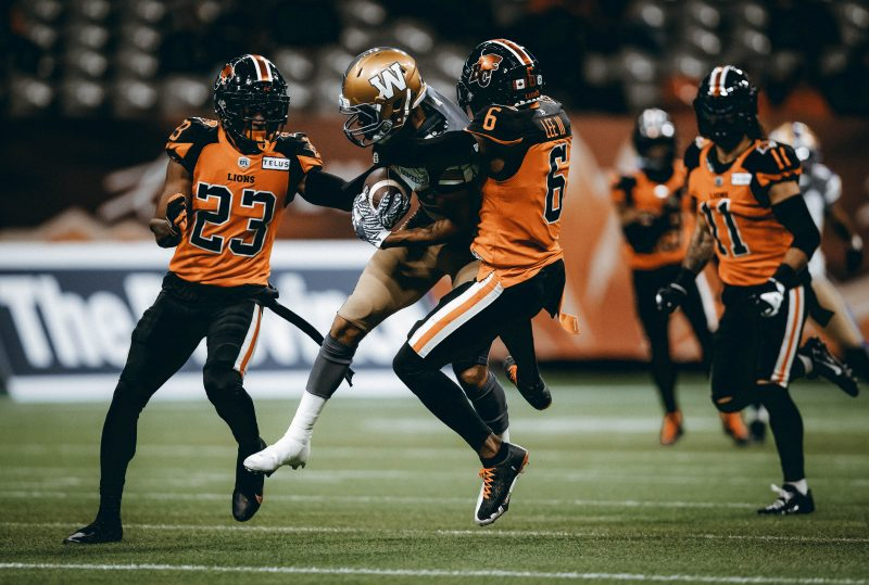 Winnipeg Blue Bombers' Kenny Lawler, second left, is tackled by B.C. Lions' T.J. Lee (6) and Anthony Thompson (23) after making a reception during the first half of a CFL football game in Vancouver, on Friday, October 1, 2021. THE CANADIAN PRESS/Darryl Dyck
