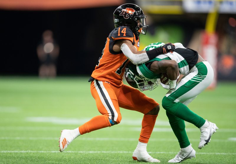 B.C. Lions' Marcus Sayles (14) tackles Saskatchewan Roughriders' Kyran Moore during the first half of a CFL football game in Vancouver, on Friday, September 24, 2021. THE CANADIAN PRESS/Darryl Dyck