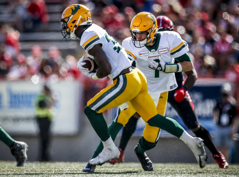 Edmonton Elks quarterback Trevor Harris, right, hands the ball off to James Wilder Jr. during first half CFL football action against the Calgary Stampeders in Calgary, Monday, Sept. 6, 2021.THE CANADIAN PRESS/Jeff McIntosh