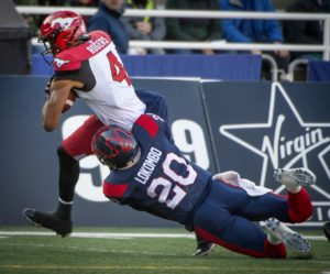 Calgary Stampeders Eric Rogers drags Montreal Alouettes Boseko Lokombo along as he is tackled during 1st half CFL action in Montreal Saturday July 20, 2019.  (CFL PHOTO - Peter McCabe)