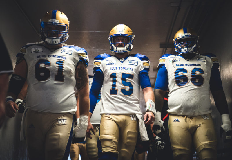 Matthias Goossen (61), Matt Nichols (15) and Stanley Bryant (66) of the Winnipeg Blue Bombers before the game against the Calgary Stampeders at McMahon Stadium in Calgary, AB on Thursday, August 25, 2018. (Photo: Johany Jutras / CFL)