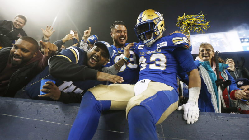 Winnipeg Blue Bombers' Andrew Harris (33) celebrates a touchdown by quarterback Chris Streveler (17) with fans during the second half of CFL action against the Calgary Stampeders, in Winnipeg, Friday, Oct. 26, 2018. THE CANADIAN PRESS/John Woods