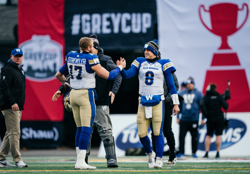 Chris Streveler (17) and Zach Collaros (8) of the Winnipeg Blue Bombers before the 107th Grey Cup game between the Hamilton Tiger-Cats and the Winnipeg Blue Bombers at McMahon Stadium in Calgary, AB, Sunday, November. 24, 2019. (Photo: Johany Jutras/CFL)