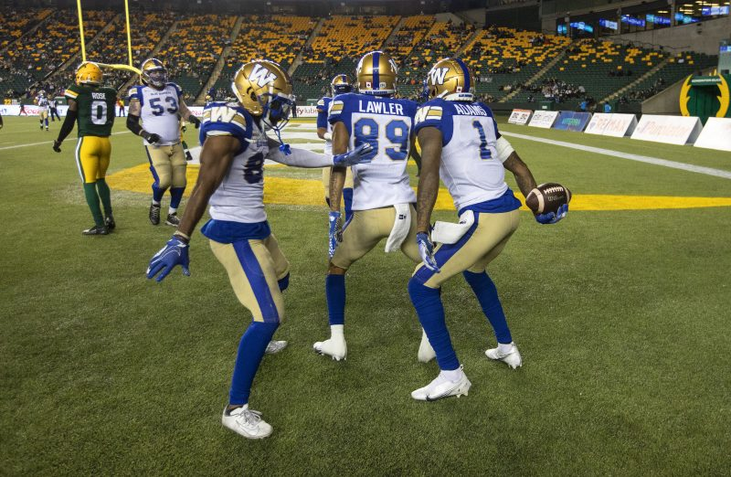 Winnipeg Blue Bombers quarterback  Zach Collaros (8), Kenny Lawler (89) and Darvin Adams (1) celebrate a touchdown against the Edmonton Elks during first half CFL action in Edmonton, Alta., on Saturday, September 18, 2021. THE CANADIAN PRESS/Jason Franson.