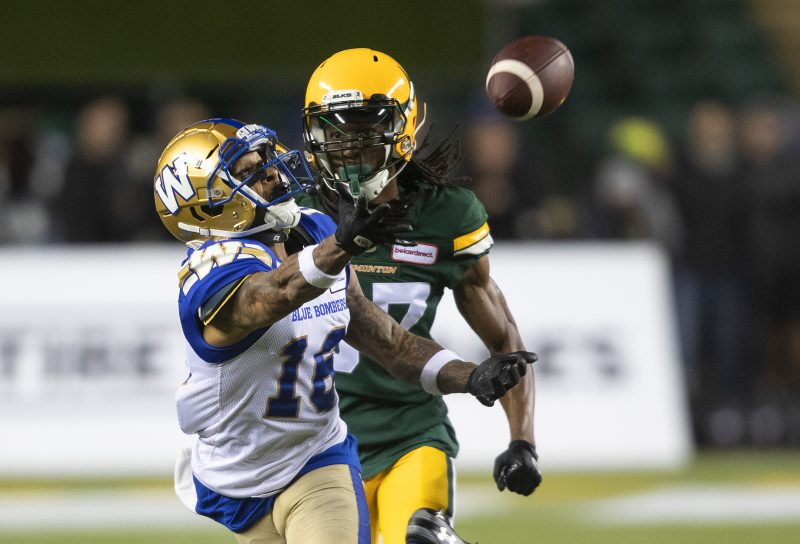 Winnipeg Blue Bombers' Mike Jones (16) reaches for the pass meant for Edmonton Elks' Derel Walker (87) during second half CFL action in Edmonton, Alta., on Saturday September 18, 2021. THE CANADIAN PRESS/Jason Franson.