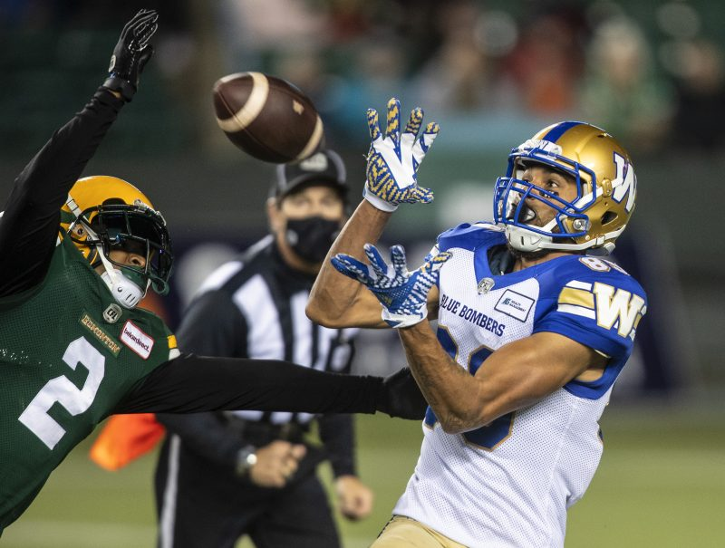 Winnipeg Blue Bombers' Kenny Lawler (89) makes the catch as Edmonton Elks' Jonathon Mincy Sr. (2) tries to stop him during first half CFL action in Edmonton on Friday, October 15, 2021. THE CANADIAN PRESS/Jason Franson.