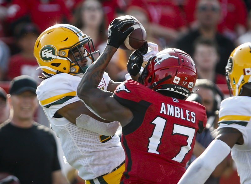 Edmonton Eskimos' Arjen Colquhoun, left, and Calgary Stampeders' Markeith Ambles battle for the ball during first half CFL football action in Calgary, Saturday, Aug. 3, 2019. THE CANADIAN PRESS/Jeff McIntosh
