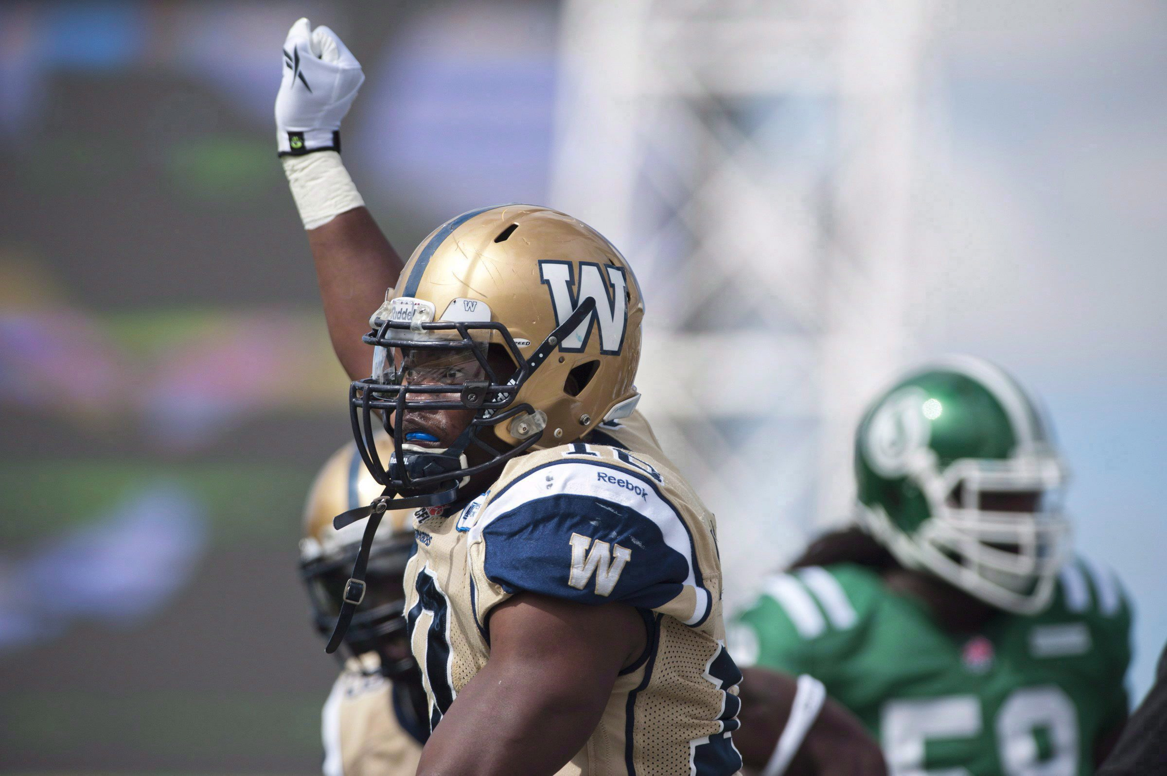 The Saskatchewan Roughriders signed national linebacker Henoc Muamba on Wednesday. Muamba, in Bombers colours, celebrates a tackle against the Saskatchewan Roughriders during CFL football action in Regina in a September 1, 2013, file photo. THE CANADIAN PRESS/Liam Richards
