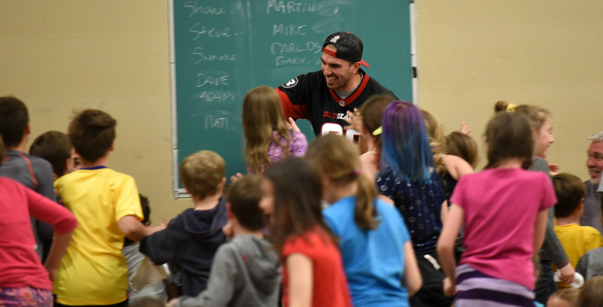 Brad Sinopoli hi-fiving school kids