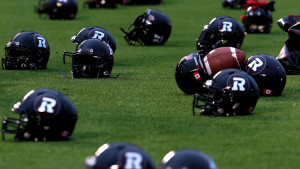 Image of REDBLACKS helmets lined up by the endzone during practice