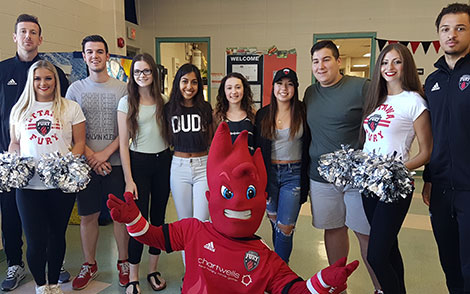 Fury players, Sparky and students posing for photos during a Lunch Bunch session